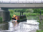 Kids on a barge going under Bamfurlong Road bridge